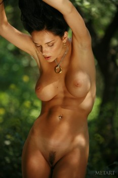Brunette teases pussy under the tree