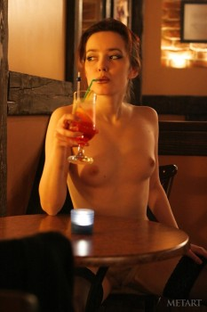 Naked cutie drinks cocktail in a bar