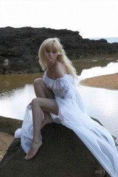 Lovely blonde is white dress is enjoying solo in water
