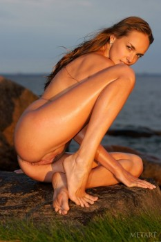 Naked babe enjoys warm sea at the sunset