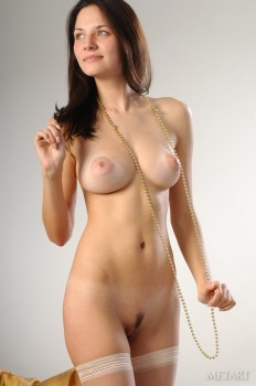 Cutie rubs naked body with long beads.