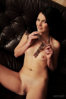 Naked dark-haired cutie masturbates on carpet.