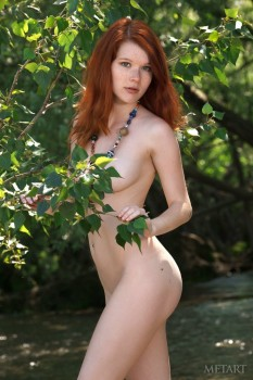 Skinny redhead getting naked in a creek