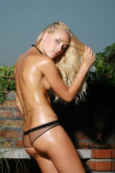 In shape, hot blonde plays in the hose outside
