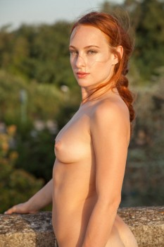 Naked red-haired cutie wanders the roof.