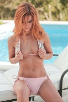 Red-haired cutie teases herself at an outdoor pool.