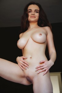 Brunette plays with big, heavy boobs in bed