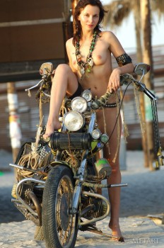 Naked biker babe with her bike at the beach