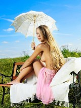 Naked hottie hides under umbrella from the hot sun