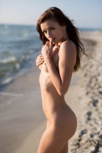 Sweetie poses naked on an isolated beach